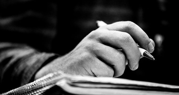 A student holds a pen poised over notebook paper during an economics class January 23, 2014 in O'Shaughnessy Educational Center.