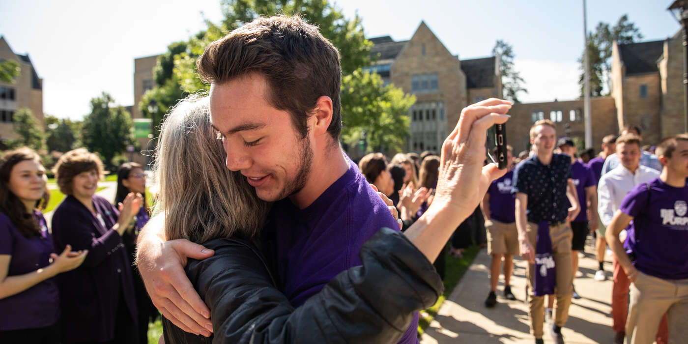 A student hugs his mother during the annual March through the Arches to celebrate the start of the school year and the arrival of a new class of freshmen on campus on September 3, 2019, in St. Paul.