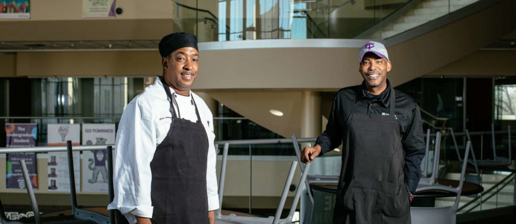 Dining services staffers Carl Littlejohn, left, and brother Anthony Littlejohn, right, pose for a photo in the Anderson Student Center. They are part of a team of critical employees ensuring that students and staff remaining on campus are looked after.
