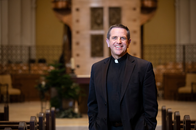 Father Christopher Collins poses for portrait in Aquinas Chapel