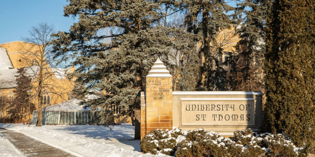 The St. Thomas monument sign on the corner of Cleveland and Summit on a cold sunny winter day on the St. Paul campus.