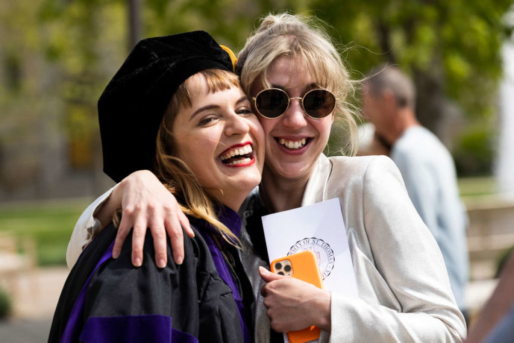 A student laughs while hugging a family member during the School of Law Class of 2021 Commencement Ceremony. Mark Brown/University of St. Thomas